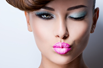 Closeup face of beautiful flirting woman with fashion bright vivid color eye makeup